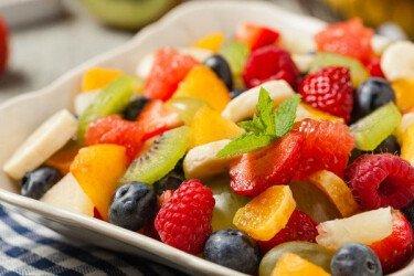 Помойте все фрукты и измельчите половину киви на более мелкие кусочки. Затем добавьте фрукты сверху слоя йогурта.